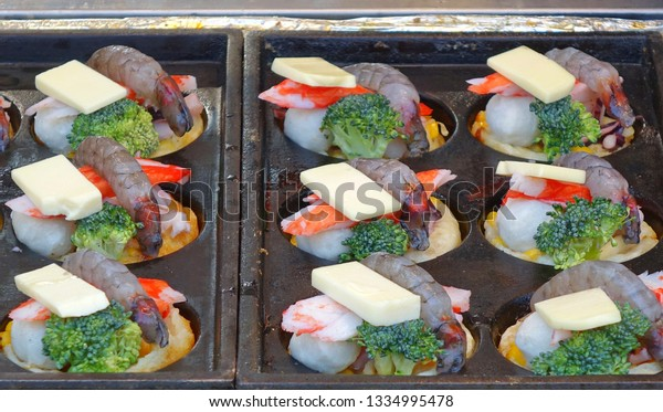 A street vendor prepares seafood, cheese and vegetables for baking