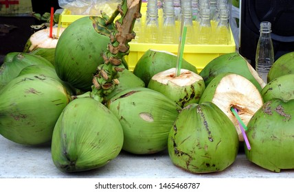 A street vendor sells fresh coconut milk straight from the fruit