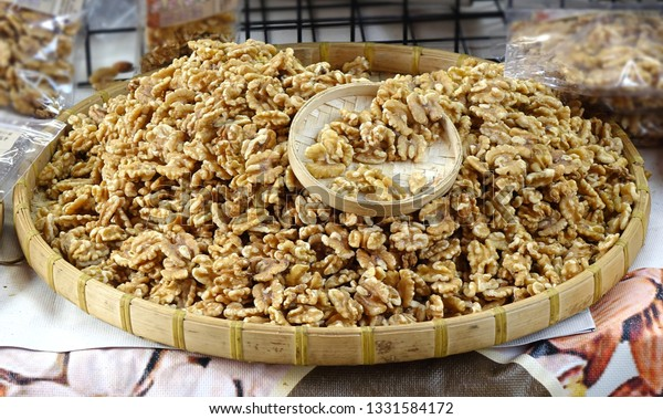 A street vendor sells fresh walnuts in a bamboo tray