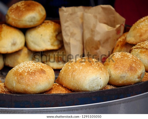 A street vendor sells freshly baked buns just out of the oven