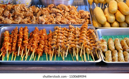 A street vendor sells fried chicken, meat skewers and corn dogs