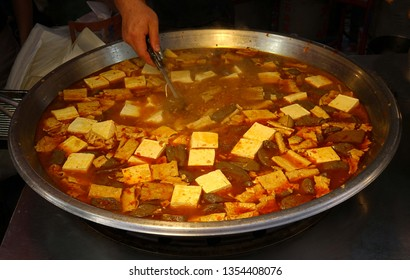 A street vendor sells a spciy stew with tofu and duck blood cakes