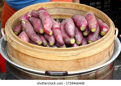 A street vendor sells sweet potatoes cooked in a bamboo steamer