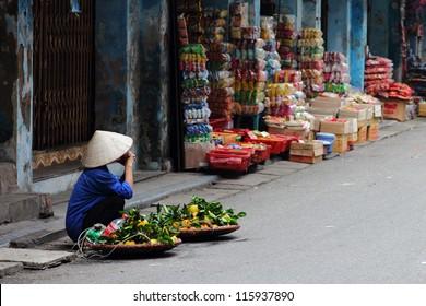 Street vendor in Vietnam selling fruit at a corner in Hanoi.