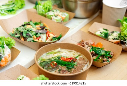 Street vendor's vegetable salads sold outdoors. Snacks closeup, in craft package. Fast food for commercial kitchen.