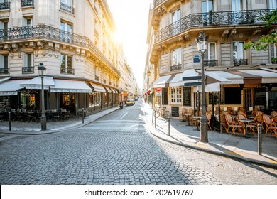 Street view with beautiful buildings and cafe terrace during the morning light in Paris