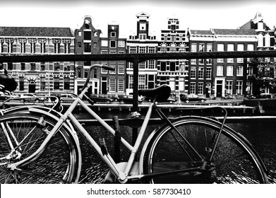 Street View with bike parked on an embankment in the historical center of Amsterdam in the Netherlands. Black and white picture