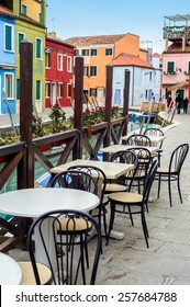 Street view of a cafe terrace with empty tables and chair on the famous island Burano, Venice, Italy.