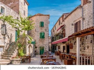 Street view of a charming outdoor tourist restaurant, open and prepared for customers, with rustic wooden furniture and surrounded by old stone buildings, in Stari Grad, Hvar Island, Croatia. - Shutterstock ID 1839642841