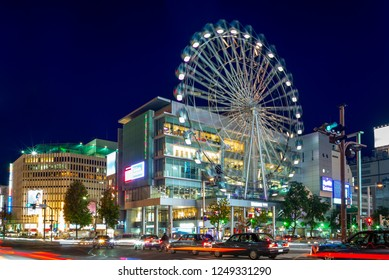 """street view of nagoya with ferris wheel in japan. the translation of the chinese characters on the traffic sign is """"Nishikidori-Otsu"""", the name of this street"""
