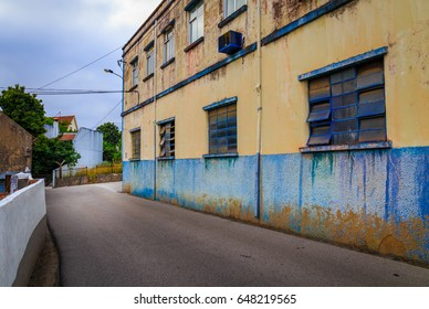 Street view of an old factory with blue windows and a dirty wall.