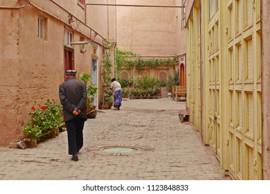 Street view of an old Muslim man walking down the street in small alley of renovated buildings zone in Kashgar Ancient Town, Xinjiang, China.
