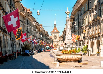 Street view on Kramgasse with fountain and clock tower in the old town of Bern city. It is a popular shopping street and medieval city centre of Bern, Switzerland