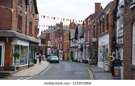 Street view with shopfronts in Knutsford, Cheshire, England on cloudy day, July 2018