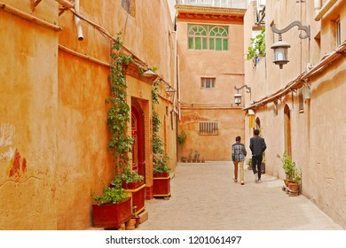 Street view of two young boys walking down the small alley in renovated buildings zone in Kashgar Ancient Town, Xinjiang, China.