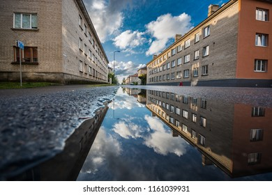 Street view with water reflection after rain in Estonia. Summer Rain Showers, urban view. Old soviet town.