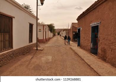 Street in a village. Adobe wall texture in San Pedro de Atacama, Chile.