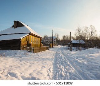 The street in the village in the winter. The house in snow