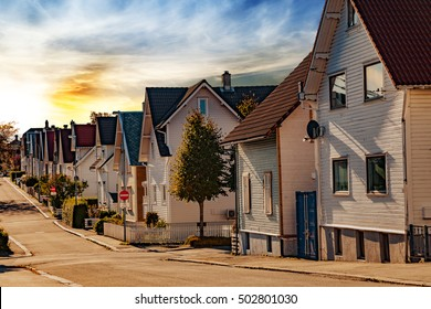 Street with white houses at sunset in Stavanger, Norway.