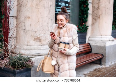 Street winter cold weather portrait of pretty fashion woman walking outdoor, chatting with smartphone and having coffee, smiling