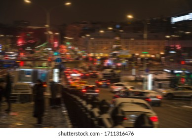 Street wit many cars by night in winter. Blurred picture