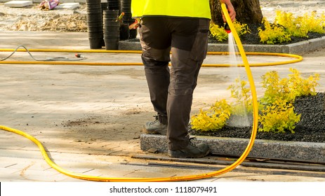 a street worker female in work clothes watering a new road and a lawn in the park with a hose-pipe. Tallinn, Estonia