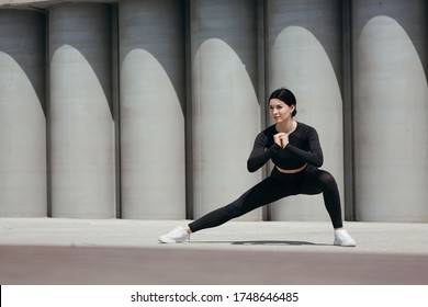 Street workout of a beautiful girl lunging for stretching inner thigh muscles.