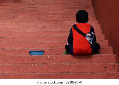 A street young Seller is sitting and waiting on the red step at a Christ Church in Melaka Malaysia