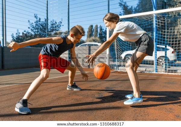 Streetball basketball game with two players, teenagers girl and boy with ball, outdoor city basketball court