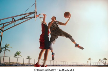 Streetball. Basketball player in action on sunset. Basketball players play in streetbol.