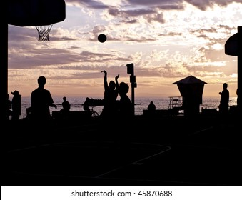 streetball player silhouettes at laguna beach california. taking a shot.