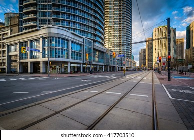 Streetcar tracks and modern buildings along Queens Quay West, at the Harbourfront, in Toronto, Ontario.