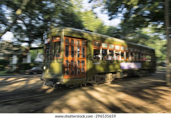 Streetcar tram running through the leafy Garden District of New Orleans at sunset