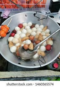 Streetfood being prepard in a sidewalk in Makati City. Enjoy a bite size of a hotdog, fishballs, quail eggs with orange breading, kikiam.