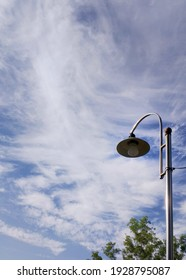 a streetlamp, clouds and sky in the background