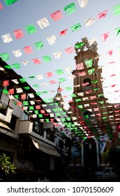 "Street-level view of Our Lady of Guadalupe through ""Dia de los Muertos"" flags in Puerto Vallarta, Mexico."