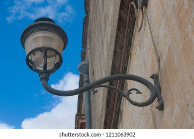 Streetlight on the wall of ancient building, South Italy
