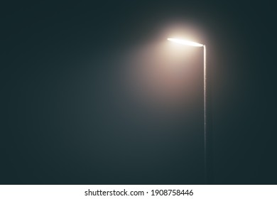 Streetlight post with bright light in a misty fog in the evening in a dramatic mood