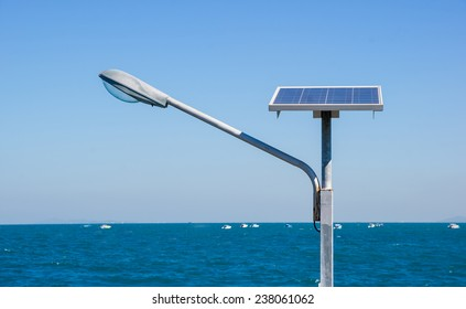 Streetlight with solar panel against sea background