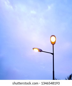 Streetlights against the blue evening sky - yellow electric lights, illumination in daytime