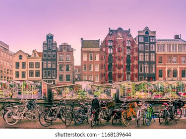 The streets of Amsterdam with bicycles, tulip shops and the iconic dancing houses along the canal.