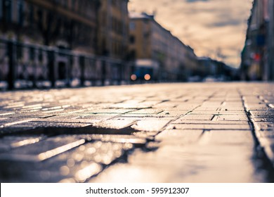 Streets in the late autumn, the empty sidewalk and headlights of the approaching car. Close up view from a puddle level on the sidewalk, image in the yellow-blue toning