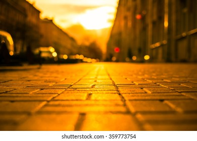 Streets in the light of the autumn sun, pedestrians walk on the sidewalk. The view from the sidewalk level, image in the orange-yellow toning