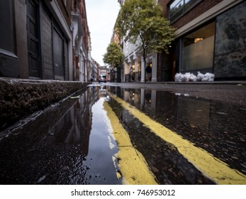 The streets of London. Shallow foreground focus on the kerbside puddle reflecting a typical London back street.
