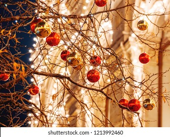 Streets of Moscow decorated for New Year and Christmas celebration. Tree with bright red and yellow balls. GUM (Main Department Store) building with light bulbs. Russia.
