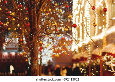 Streets of Moscow decorated for New Year and Christmas celebration. Tree with bright red and yellow balls. Buildings with light bulbs. Russia.