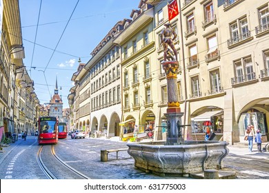Streets with shopping area and fountain in the historic old medieval city centre of Bern, Switzerland.