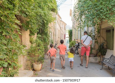 Streets of the village of Cucuron, in the Luberon, France. All its doors and windows are painted with pastel colors. Family walking through its streets.