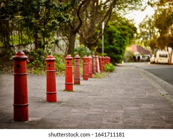 Streetscape photography of vintage red painted bollards on a street in Crows Nest, Sydney NSW Australia