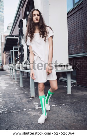 2b433688325d8 Streetstyle, fashion. Teenager in white dress standing on the street.  Propellers on background